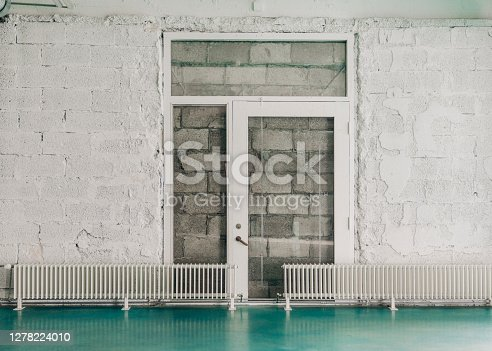 Radiators against white wall at entrance hall. Glass door is against concrete blocks.