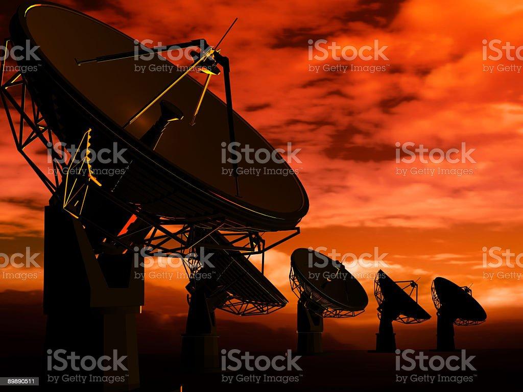 Radio antennas in orange sunset background royalty-free stock photo