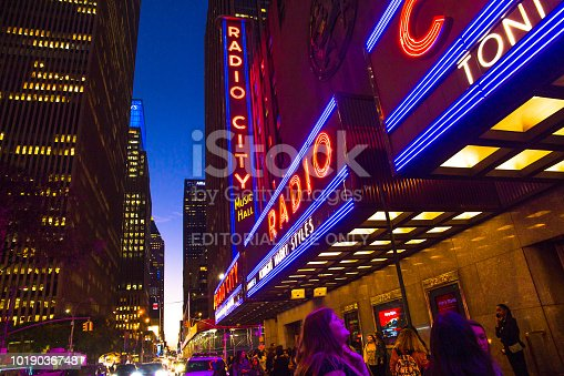 New York City, New York, USA - September 28, 2018: Bright lights of the Radio City Music Hall sign as seen at night from the sidewalk,