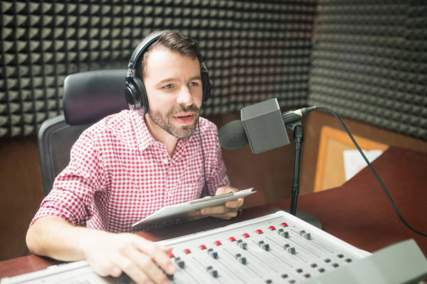 Radio jockey hosting show live on radio Handsome young man with beard hosting show live on radio station radio dj stock pictures, royalty-free photos & images