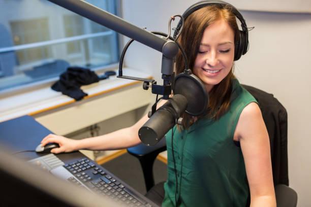 radio jockey smiling while wearing headphones in studio - radio dj stock photos and pictures