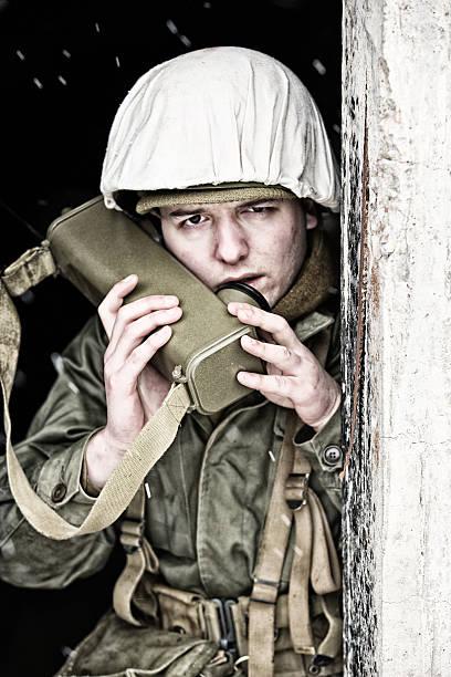 WWII Radio Man Calling In Strike From Bunker In Winter - foto de acervo