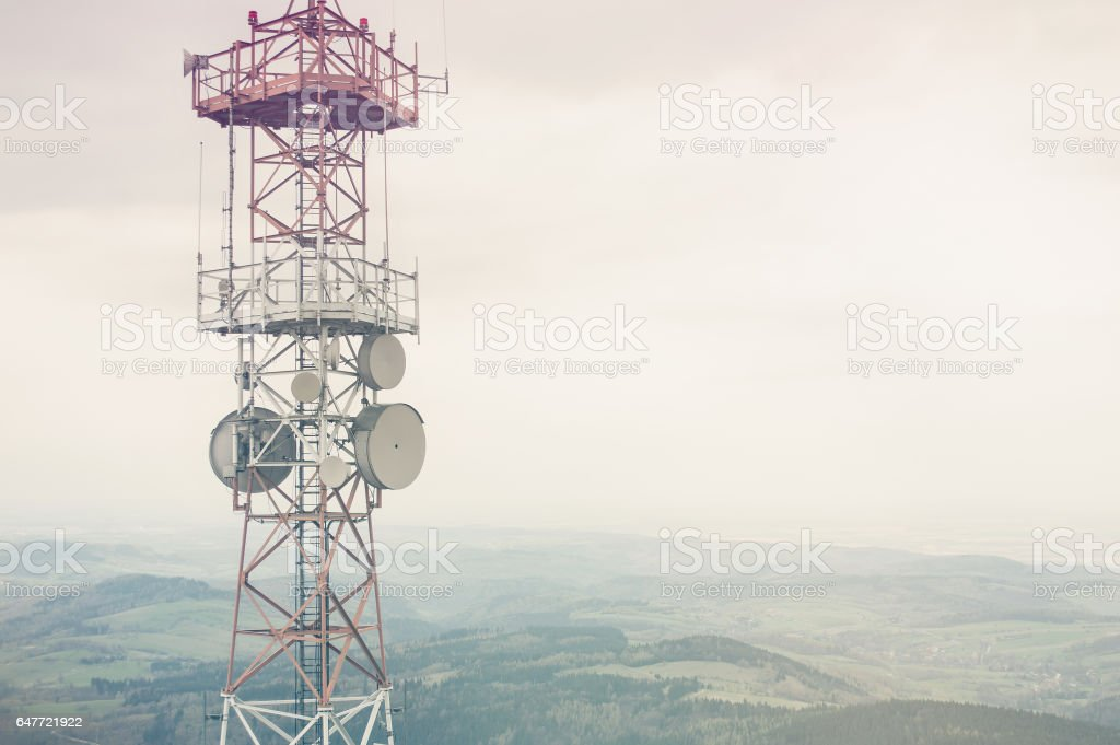 Radio mast over a cloudy valley background stock photo