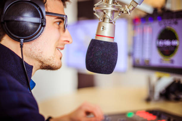 Radio moderator is sitting in a modern broadcasting studio and talking into the microphone Young man in the broadcasting studio, radio, talking into the microphone radio dj stock pictures, royalty-free photos & images