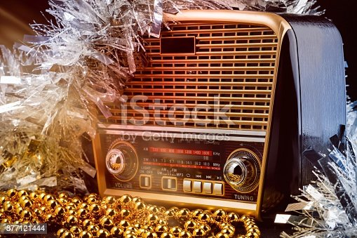 modern retro styled radio with audio player and colored christmas decorations on black background. Toned light effects