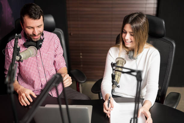 radio station coworkers running a live show - trasmissione radiofonica foto e immagini stock