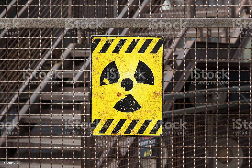 radioactive warning sign on rusty fence stock photo