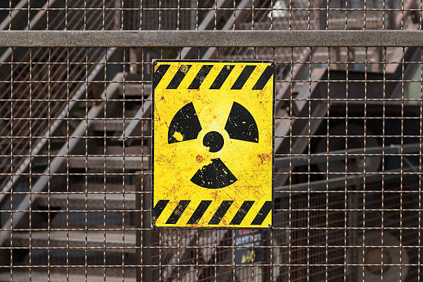 radioactive warning sign on rusty fence yellow radioactive warning sign on rusty fence radioactive contamination stock pictures, royalty-free photos & images
