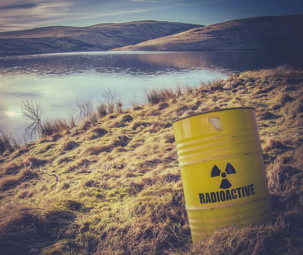 Radioactive Waste Near Water Conceptual Image Of A Radioactive Nuclear Waste Barrel Or Drum Near Water In The  Countryside radioactive contamination stock pictures, royalty-free photos & images