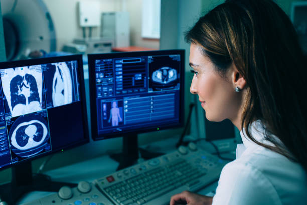 Radiologist reading a CT scan. Female doctor running CT scan from control room at hospital Radiologist reading a CT scan. Female doctor running CT scan from control room at hospital medical x ray stock pictures, royalty-free photos & images