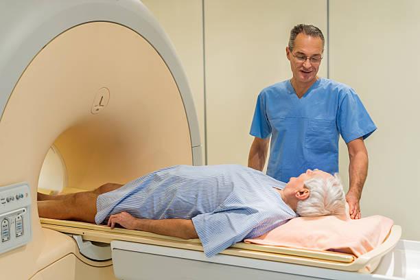 radiologe gespräch mit senior patienten im magnetresonanztomographie. - strahlung stock-fotos und bilder