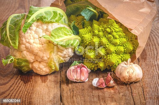 Romanesco broccoli with cauliflower and garlic in a paper bag on a wooden table.