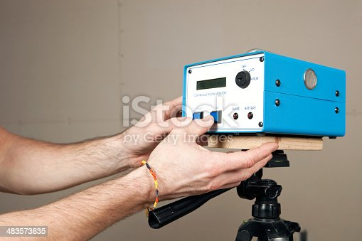 Hands programming a continuous radon monitor mounted to a tripod in an unfinished house basement. A house is commonly tested for radon with a single use test kit. If initial readings are high or remediation work has begun a system like this isz used to determine a more accurate measurement over time. An added benefit of this unit is real time measurement. The display screen reads Rate 2.3 pCi/l  (picocuries per liter), the curie is a unit of radioactivity. The background is unfinished drywall with seams and screws.