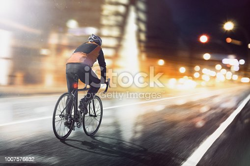 Radsportler fährt durch beleuchtete Stadt