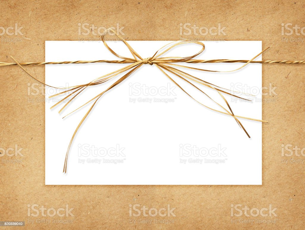 Raffia bow and a card tied on craft paper stock photo