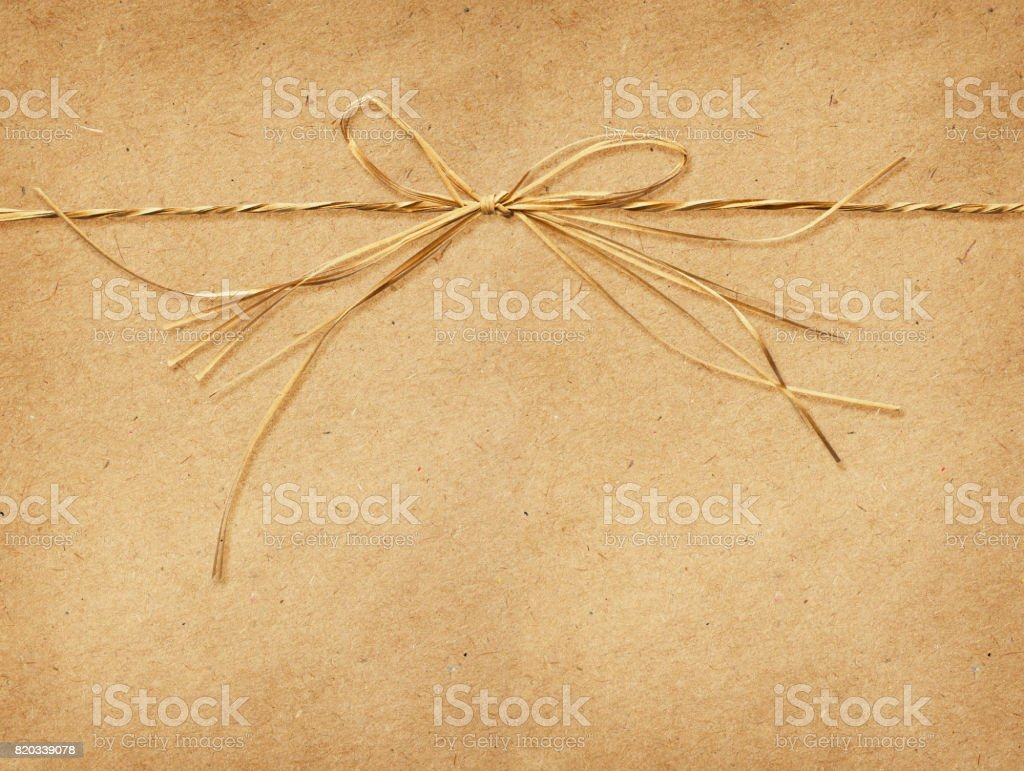 Raffia bow tied on craft paper stock photo