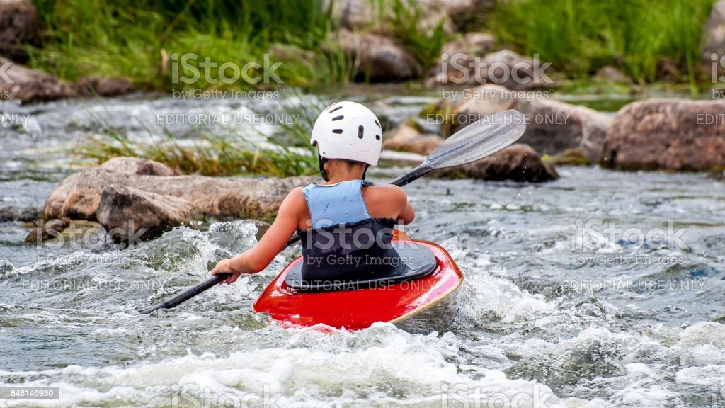 Rafting and kayaking. A very young athlete improves his skills in running a kayak on a river with a rapid current. stock photo