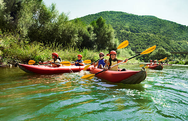 rafting calm water canoes Several two people team inflatable canoes rafting in a calm waters with beautiful surrounding. canoeing stock pictures, royalty-free photos & images