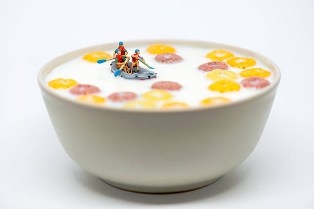 rafting in a bowl of colorful cereal with milk. - figurine stock photos and pictures