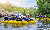 A group of people rafting on a stormy river in the yellow rafts fully loaded with personal belongings. Myhiya, Ukraine June 12, 2018: Rafting, kayaking. Ecological water tourism.