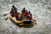 Verona, Italy - Sept 19th, 2020: Rafting on white water, a group of people, children and adults, with an instructor on an inflatable raft in the River Adige in Verona downtown, Veneto, Italy, Europe.