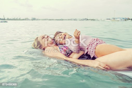 Cute kid and a woman on a raft in the ocean, smiling, playing and having fun