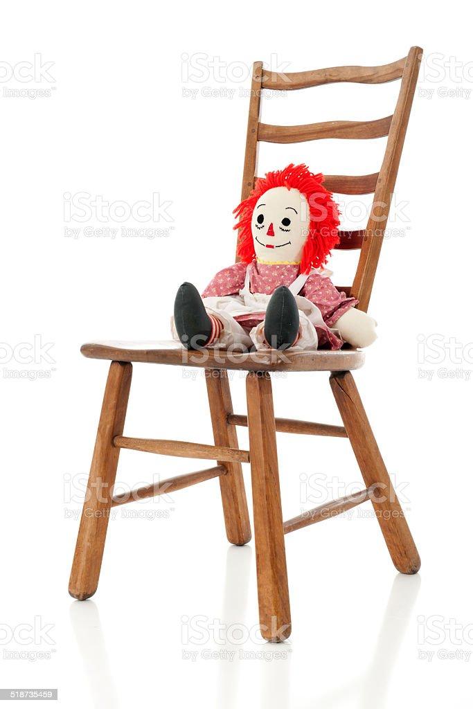 Boneca de Pano em uma escada de uma cadeira - foto de acervo