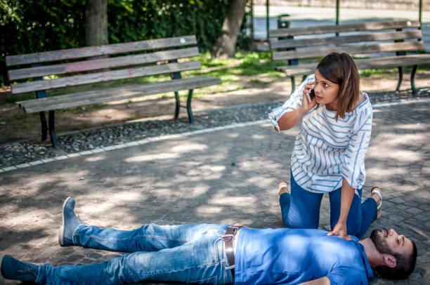 Ragazza soccorre ragazzo incosciente e chiama ik servizi di emergenza e l'ambulanza foto