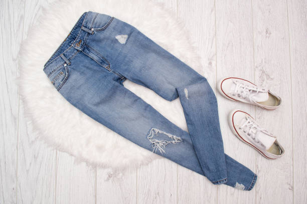 Ragged blue jeans and white sneakers on white fur. Fashionable concept Ragged blue jeans and white sneakers on white fur. Fashionable concept skinny jeans stock pictures, royalty-free photos & images