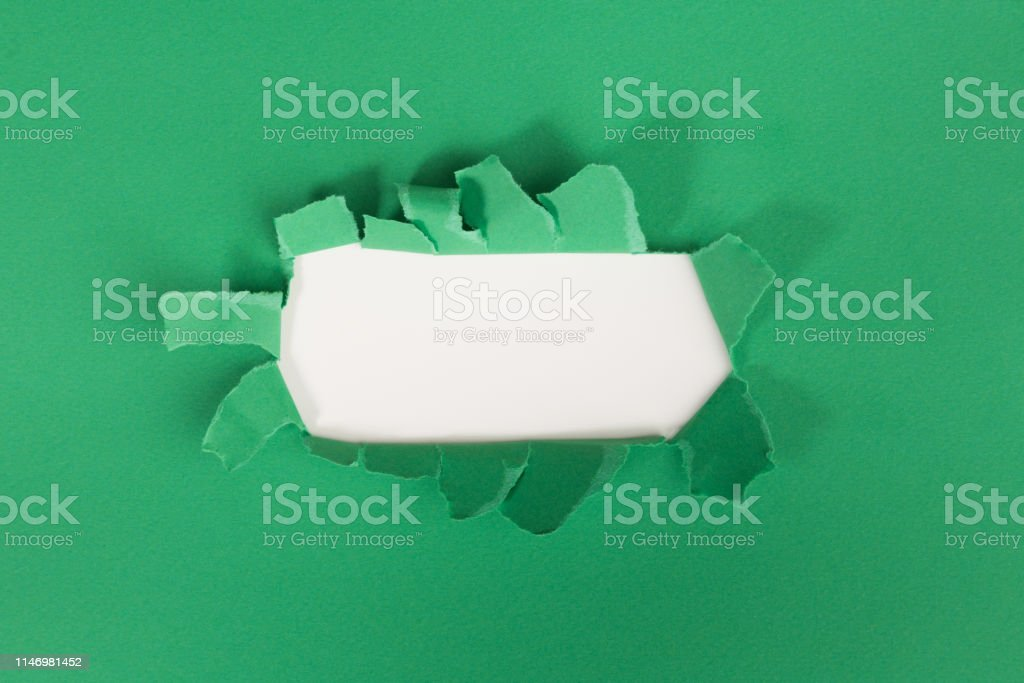 ragged Hole torn in ripped paper on green background