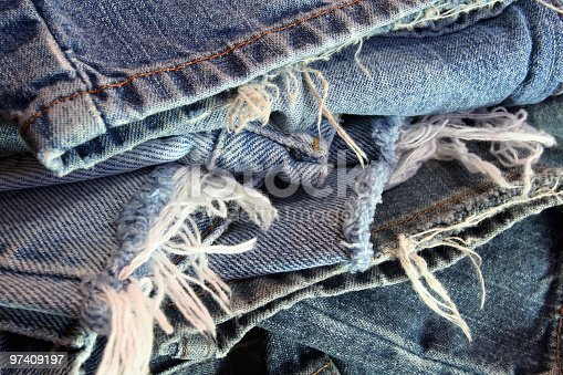 An abstract pile of several different pairs of ragged old blue jeans ready to be recycled.