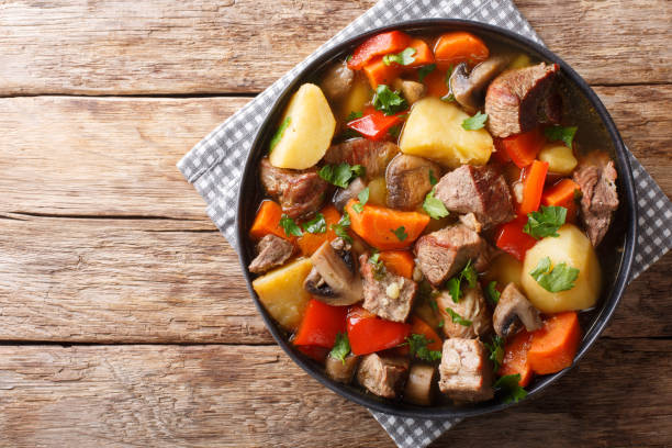 ragout of pork with mushrooms and vegetables close-up on a plate. horizontal top view ragout of pork with mushrooms and vegetables close-up on a plate on the table. horizontal top view from above ragout stock pictures, royalty-free photos & images