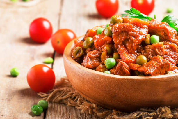 Ragout with beef, carrots, green peas and tomatoes, old wooden table, selective focus Ragout with beef, carrots, green peas and tomatoes, old wooden table, selective focus ragout stock pictures, royalty-free photos & images