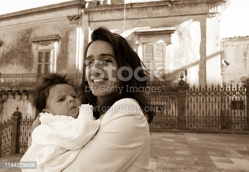Ragusa, Sicily, Italy: A mother holds her baby outside the Basilica of San Giorgio in Ragusa Ibla, Sicily, a UNESCO World Heritage Site.