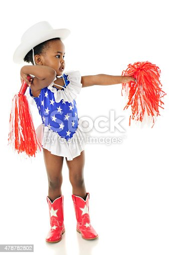 An adorable two year old in a star studded red, white and blue outfit cheering with her pom-poms for the USA.  On the white background.