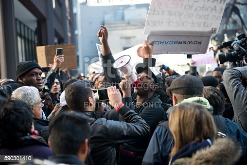 Chicago, Illinois, USA - December 9th 2015:  A Black Lives Matter protestor, surrounded by a crowd, during the Rahm resign protest.