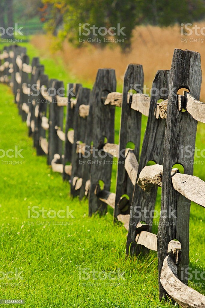 Split rail wood fence posts trail off into the distance forming a...