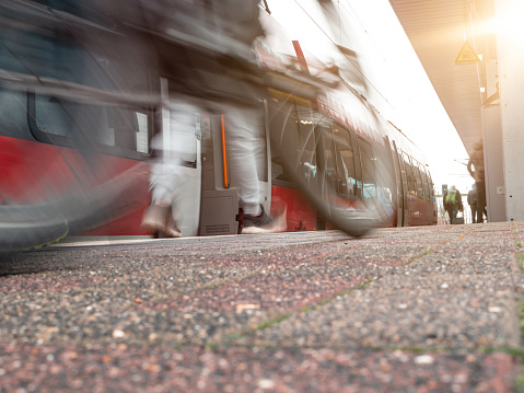 rail platform with red commuter train in motion blur, man with mike blurred in foreground