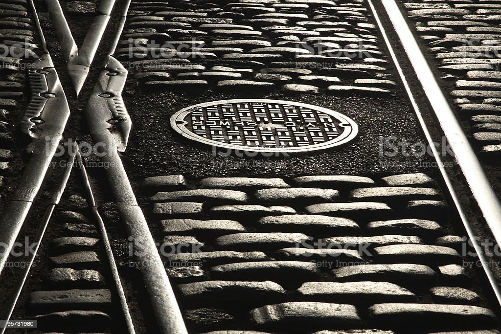 Rail tracks and manhole cover on cobbled street royalty-free stock photo