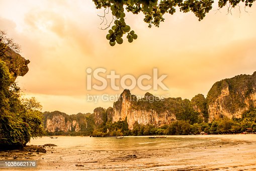 Railay beach Ao Nang. Rainy weather with clouds, warm colors. View on the beach, sea and a mountain range.