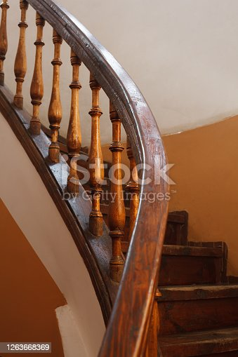 Railings of steep antique wooden staircase with selective focus