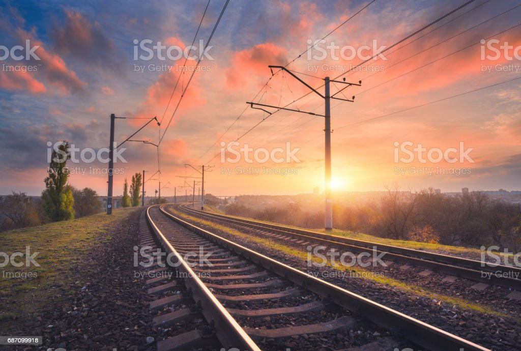 Railroad and beautiful sky at sunset. Industrial landscape with railway station, colorful blue sky with red clouds, trees and green grass, yellow sunlight in summer. Railway junction. Heavy industry stock photo