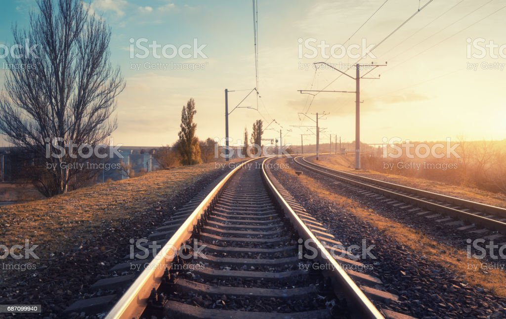 Railroad and beautiful sky at sunset. Industrial landscape with railway station, colorful sky, trees and yellow sunlight. Railway junction. Heavy industry. Railways. Cargo shipping. Vintage style Lizenzfreies stock-foto