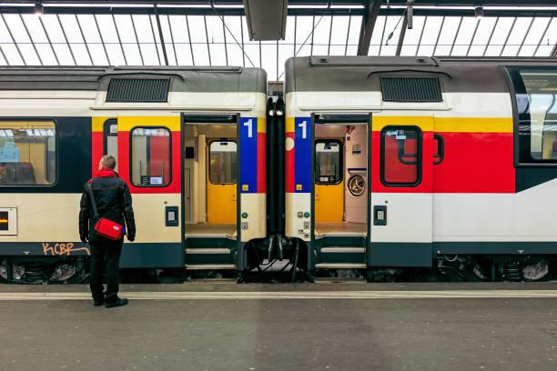 railroad cars of a passenger train standing at a platform of the zurich main railway station - konduktor pociągu zdjęcia i obrazy z banku zdjęć