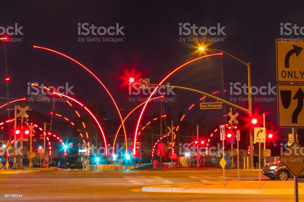 Railroad Crossing During The Night With Motion Gates Stock Photo - Download  Image Now