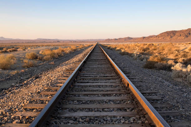 Railroad Crossing in California desert at Trona Pinnacles Railroad tracks and crossing in the California desert tramway stock pictures, royalty-free photos & images