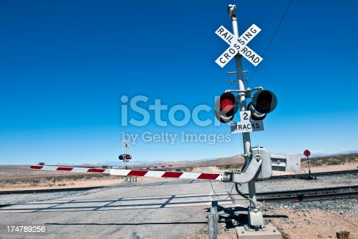 Level crossing barrier with red signal on Cuttof Rd, Death valley National Park, California, Western USA.