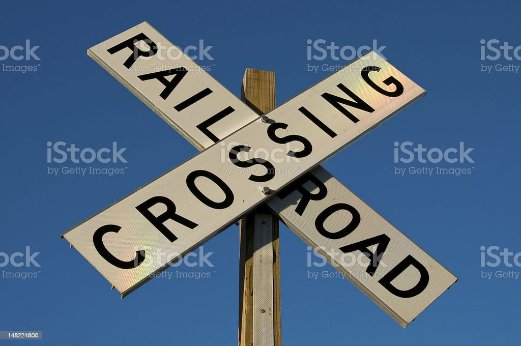 Railroad Crossing Sign with Rainbow lighting Photo of a railroad crossing sign out in the country.  The sun was setting and projected a rainbow light pattern onto the sign. Crossing Stock Photo