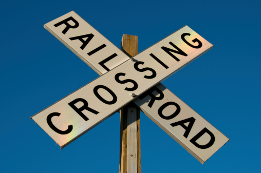 Railroad Crossing Sign With Rainbow Lighting Stock Photo - Download Image Now