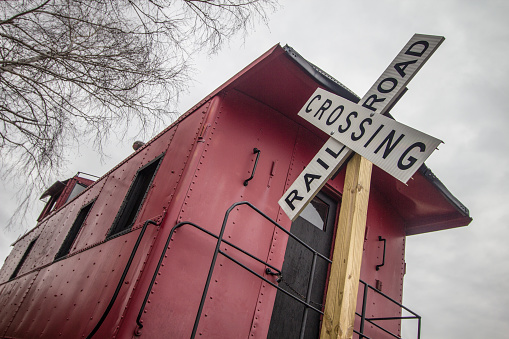 Railroad Crossing Sign With Vintage Red Caboose In The Rural American Midwest